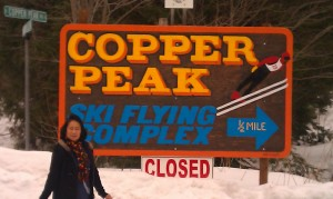 Lorie poses in front of hte Copper Peak sign