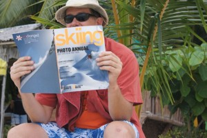 Man reading Skiing Magazine on a tropical beach -- Project A Squared
