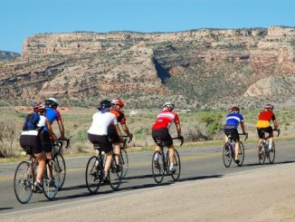 Group Riding Culture -- group of cyclists with a rocky desert plateau in the background