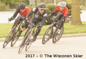 Group Riding Culture -- Three Cyclists racing around a corner