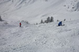 Looking down a steep ski run with skiers