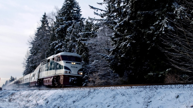 Training to Ski -- Am image of an Amtrak train with snow and pine trees
