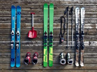 ski equipment -- skis, boots, and deep snow gear against rustic wood panel background