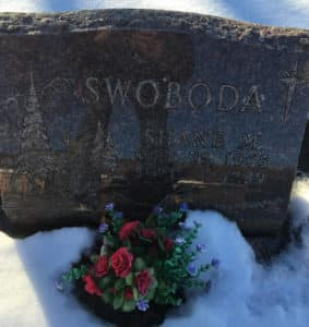 a tombstone surrounded by snow